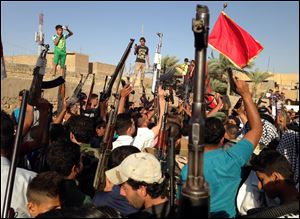 Shiite tribal fighters raise their weapons and chant slogans against the al-Qaeda-inspired Islamic State of Iraq and the Levant in the east Baghdad neighborhood of Kamaliya, Iraq, Sunday.