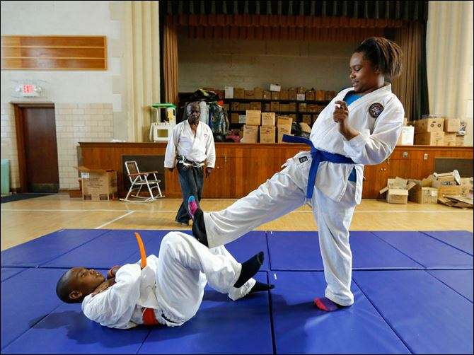 CTY karate05p1  Iesha Matthews, 12, practices with Timothy Hicks, 11, as instructor Lowell Cherry, Jr., watches during a martial arts class. Mr. Cherry started taking martial arts classes in 1972.