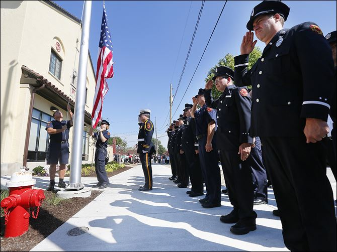 n3station-6 Jeff Koenigseker, center, a firefighter and honor guard commander, joins members of Toledo Fire and Rescue in saluting the flag during the reopening of Station 3, which closed in 2012. Pvts. Jamie Dickman and Stephen Machcinski, who died in the line of duty in January, belonged to Station 3.