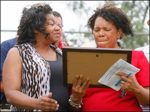 Sheila Daniels, left, gives Councilman Paula Hicks-Hudson, a plaque for her work.