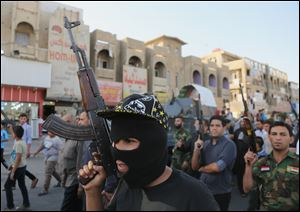 Shiite tribal fighters raise their weapons and chant slogans against the al-Qaeda-inspired Islamic State of Iraq and the Levant in the northwest Baghdad's Shula neighborhood, Iraq, Monday.