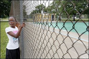 Trinity Temple, 9, and her twin brother, Cincere Temple, 9, back, look at Wilson Pool during a news conference in North Toledo. The city council approved a $73,700 budget on Tuesday that will allow the pool to open.