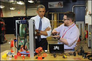 President Obama listens as Andy Leer demonstrates how a 3D printer works during a visit to TechShop Pittsburgh in Bakery Square. The President was in Pittsburgh on Tuesday to speak about spurring innovation by opening local and federal facilities to entrepreneurs.