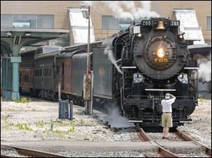 A train enthusiast photographs the front of the Nickel Plate 765.