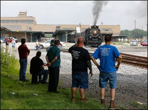 Train enthusiasts line the track.