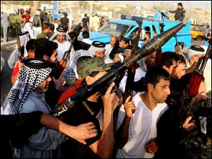Iraqi Shiite tribal fighters raise their weapons and chant slogans against the al-Qaeda-inspired Islamic State of Iraq and the Levant, after authorities urged Iraqis to help battle insurgents, in Baghdad's Sadr city, Iraq.