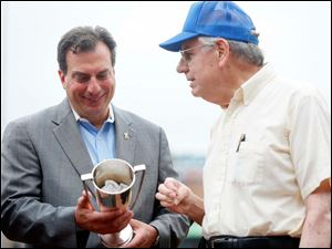 Joseph D. Napoli, general manager of the Mud Hens, left, accepts a 1920 trophy from Roger Bresnahan, right, the great nephew of Roger Philip Bresnahan, nicknamed