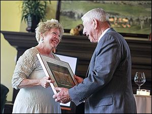 Kathy Carroll, left, presents Dick Anderson, right, with a framed picture with signatures from everyone in the Toledo Symphony during the reception for the Toledo Symphony held at the Inverness Club.