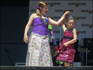 Nia Gribbons, 11, left, spins Alexis Shuttleworth, 8, right, while modeling their dresses, which are made of Duck Tape, on stage during the fashion show,
