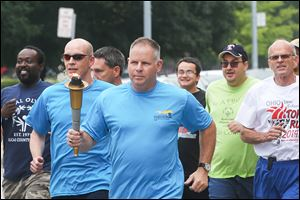 Toledo Deputy Chief George Kral, center, carries the torch as he leads officers and Special Olympians from the downtown Safety Building to Fifth Third Field. It's part of a week-long run in which police pass off the '‍Flame of Hope' torch from one jurisdiction to the next, ending in Columbus.