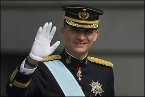 Spain's newly crowned King Felipe VI waves upon his arrival at the Parliament in Madrid, Spain.