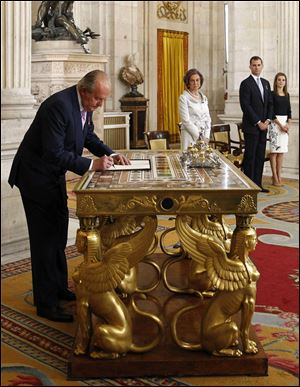 Spain's King Juan Carlos, left, signs an abdication law in the presence of Queen Sofia, Spain's Crown Prince Felipe and Princess Letizia  during a ceremony at the Royal Palace Wednesday.  Juan Carlos formally ratified the law, signing a legislation setting out the legal framework for the handover so his 46-year-old son can be proclaimed King Felipe VI.