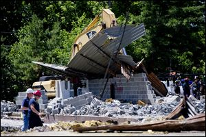 Investigators, left, walk around the scene of a fatal building collapse today in Cherry Hill, N.J.