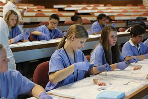 Chole Lammers, 14, of Miller City, center, practices suturing a pig's foot during class at the University of Toledo's Health Science Campus, the former Medical College of Ohio. This was the 17th year of UT's annual CampMed program. Forty-five students going into ninth grade participated this year.