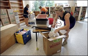 Ann Miller, foreground, a second-grade teacher, packs boxes for her classroom's move from Old Fort to Bettsville. She is assisted by  third-grade teacher Kim Warren, back left,  and first-grade teacher Melissa Reineck. With the districts' merger, the Bettsville building will house elementary students.