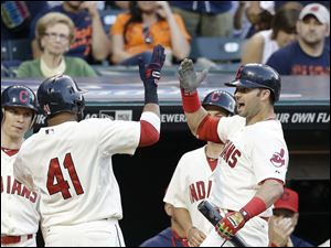 Cleveland Indians' Carlos Santana, left, celebrates with Nick Swisher after Santana hit a solo home run off Detroit Tigers starting pitcher Justin Verlander.