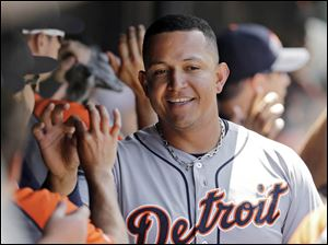 Detroit Tigers' Miguel Cabrera celebrates in the dugout after scoring on J.D. Martinez's two-run double.
