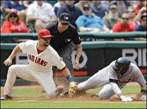 Detroit Tigers' Nick Castellanos, right, beats the tag by Cleveland Indians third baseman Lonnie Chisenhall, front left, on a wild pitch.