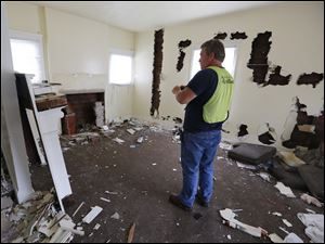 Scott Ferris, a field technician for the Lucas County Land Bank, inspects a home at 2806 Fulton Street in Toledo.