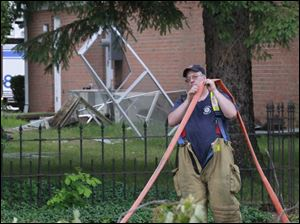 A firefighter wraps up a hose outside the home.