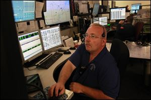 Lucas County EMS dispatcher Richie Etts, left, works on a computer as Bob Wilt, right, takes a call at the Lucas County 911 Dispatch Center on Monroe Street in Toledo on Friday.