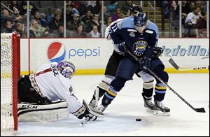 Caption: Walleye's Brett Perlini (11) takes a shot against Gwinnett goalie Josh Unice (1) during an ECHL hockey game Saturday, 03/22/14, at the Huntington Center.
