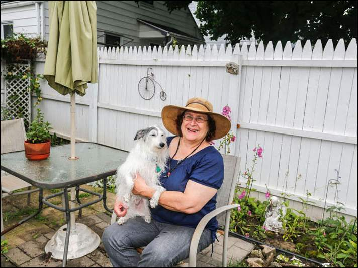 Carol Ann Erford and her dog Scrappy out in her garden at her South Toledo home.