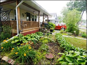 The front yard of the house, including Stella de Oro daylilies, hostas, and dianthus.