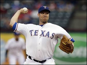 Texas Rangers starting pitcher Colby Lewis works against the Detroit Tigers.