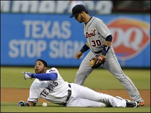 Texas Rangers' Elvis Andrus lays on the ground after being called out as Detroit Tigers shortstop Eugenio Suarez searches for the ball.