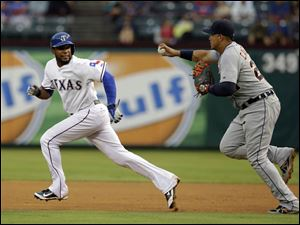 Texas Rangers' Elvis Andrus attempts to evade a tag by Detroit Tigers' Miguel Cabrera, right.