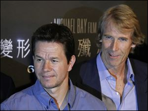 Mark Wahlberg and director Michael Bay pose before a news conference for '‍Transformers 4: Age of Extinction' on Friday in Hong Kong.