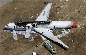 The wreckage of Asiana Flight 214 lies on the ground after it crashed at the San Francisco International Airport in San Francisco on June 6, 2013.
