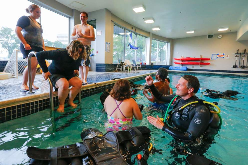 Aqua-Hut-instructor-Tom-Hites-right-helps-students-into-the-water-CTY-scuba26p
