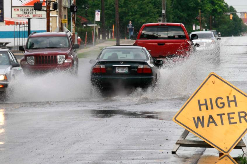 Cars-warned-by-signs-put-up-by-city-workers-slowly-drCTY-flood25p