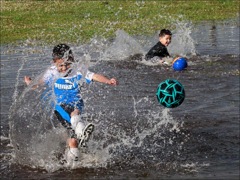 Toledoans Diego Mosqueda, 7, and his brother Tavio Mosqueda, 4, play soccer in the flooded front yard of DeVeaux Elementary School.