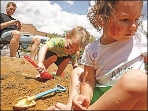Twins Atticus, left, and Madeline play in a giant sandbox during last year's Sand-Tastic! at Levis Commons.