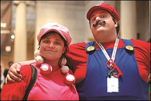 Nicole Klatt, left, dressed as Toadette, and Bill Carter, right, dressed as Mario, enjoy the video game inspired exhibit.