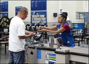 Conquisia Tyler, right, gives change to a customer at Sam's Club in Bentonville, Ark. Consumer spending rose just 0.2 percent last month after no gain in April.