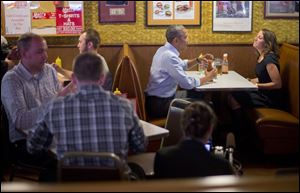 President Barack Obama sits down to have lunch with Rebekah Erler today at Matt's Bar in Minneapolis, Minn. Erler wrote the White House about her struggles to make ends meet.
