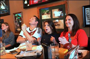 '‍We're a house divided,' Joerg Birkelbach, left, said. Mr. Birkelbach, who supports Germany, grimaces as his team's attempt on goal is thwarted by the United States while his girlfriend Rebecca Bovier of North Toledo and her daughter Malia Huss, 11, cheer on America during Thursday's World Cup match at the Blarney Irish Pub & Grub in Toledo. The United States lost to Germany 1-0.