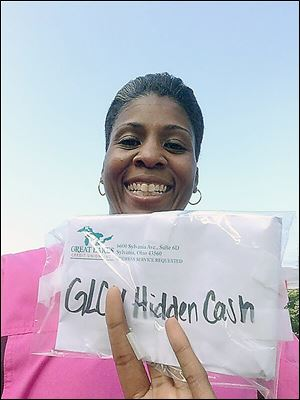 In this photo taken from Twitter, Erica Banks shows her winnings of the Hidden Cash scavenger hunt sponsored by the Great Lakes Credit Union. Ms. Banks tweeted a photo at 5:50 a.m. Thursday after she made her find near the Toledo Museum of Art.