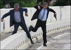 Lucas County commissioner Pete Gerkin, left, and Sen. Sherrod Brown hop over a highway barrier on their way to a press conference at the Anthony Wayne Bridge in Toledo.