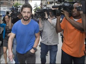 Shia LaBeouf walks through the media Friday in New York after leaving Midtown Community Court following his arrest the previous day for yelling obscenities at the Broadway show '‍Cabaret.'