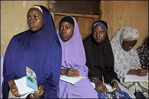 Maimuna Abdullahi, left, listens during class as she and others attend school in Kaduna, Nigeria. Maimuna is one of thousands of divorced girls in Nigeria who were married as children and then got thrown out by their husbands or simply fled.