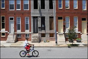 A youth rides a bicycle past a blighted property that will be restored by Come Home Baltimore. The run-down unit is sandwiched between renovated properties on North Bond Street in Baltimore's Oliver neighborhood.
