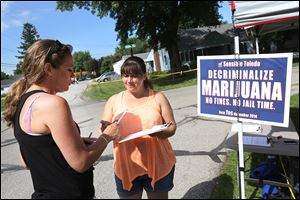 West Toledo resident Ivy Villarreau, left, talks with Northwest Ohio NORML secretary Kelley Dellinger  near the June 21 Point Place Days Summer Fest after signing a petition to put an initiative decriminalizing marijuana use in the city of Toledo on the November ballot.