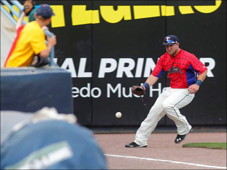 Mud Hens player Tyler Collins chases a ball hit by Columbus Clippers player Audy Ciriaco.