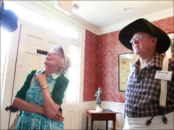 Martha Baldoni, left, looks at items on a wall in the Spafford House Museum with Frank Butwin, right, during the house's grand opening in Perrysburg on Saturday, June 28, 2014.