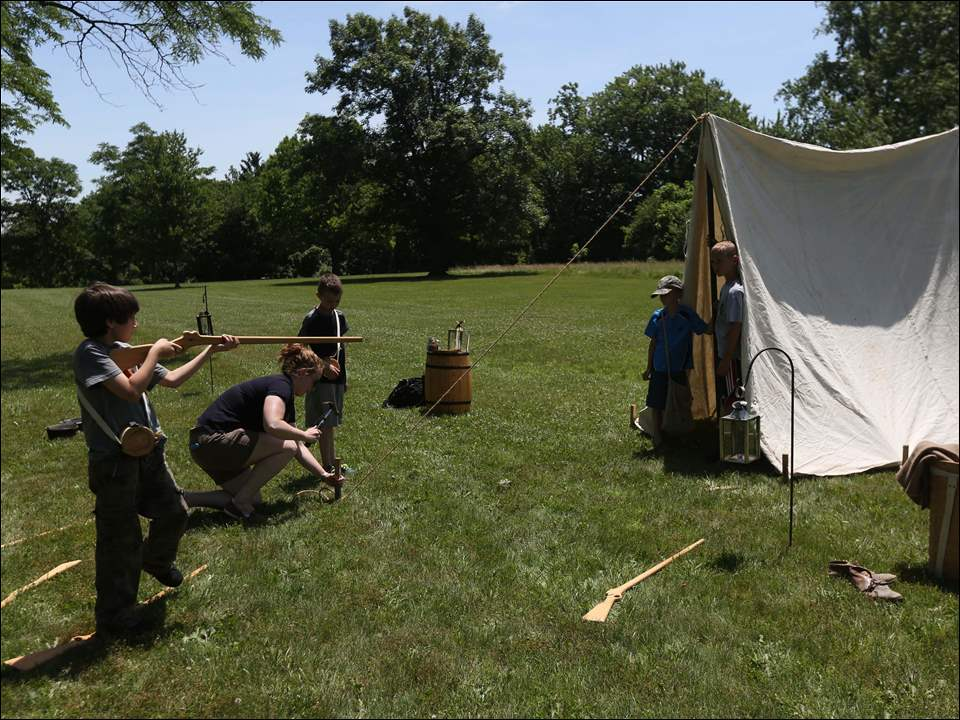 As Gage Winebernner, 10, left, takes a closer look at his wooden musket, Toledo Metroparks program production specialist Jennifer Christensen, center left, works to erect a tent.